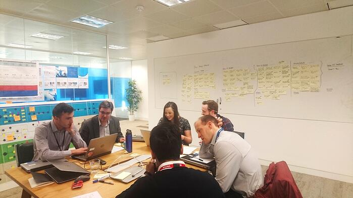 testing session with 6 people around a table and post-it on wall
